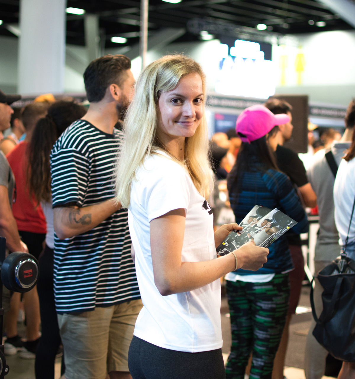 A smiling brand ambassador distributing flyers to people attending an event