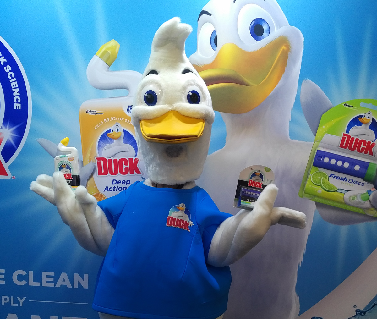 A mascot character performer posing with a product during a trade show