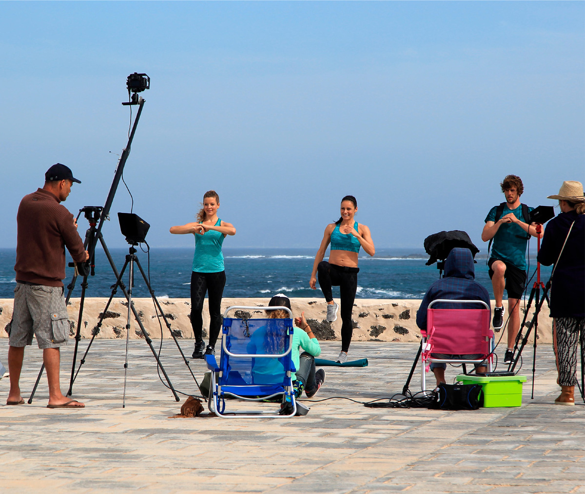 Promotional models conducting a demonstration on the beach in front of a camera crew