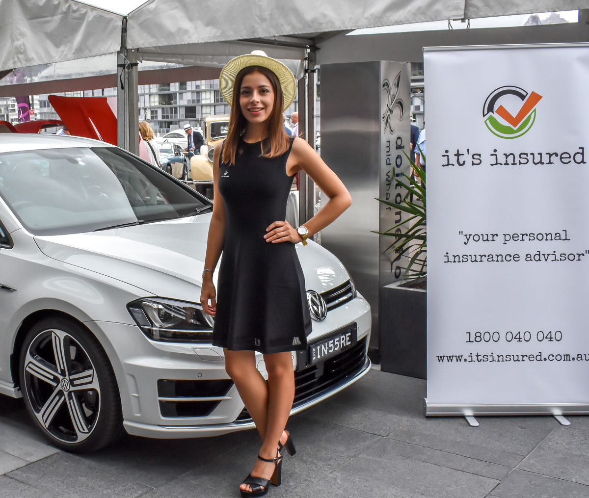 A promotional model posing with a white car