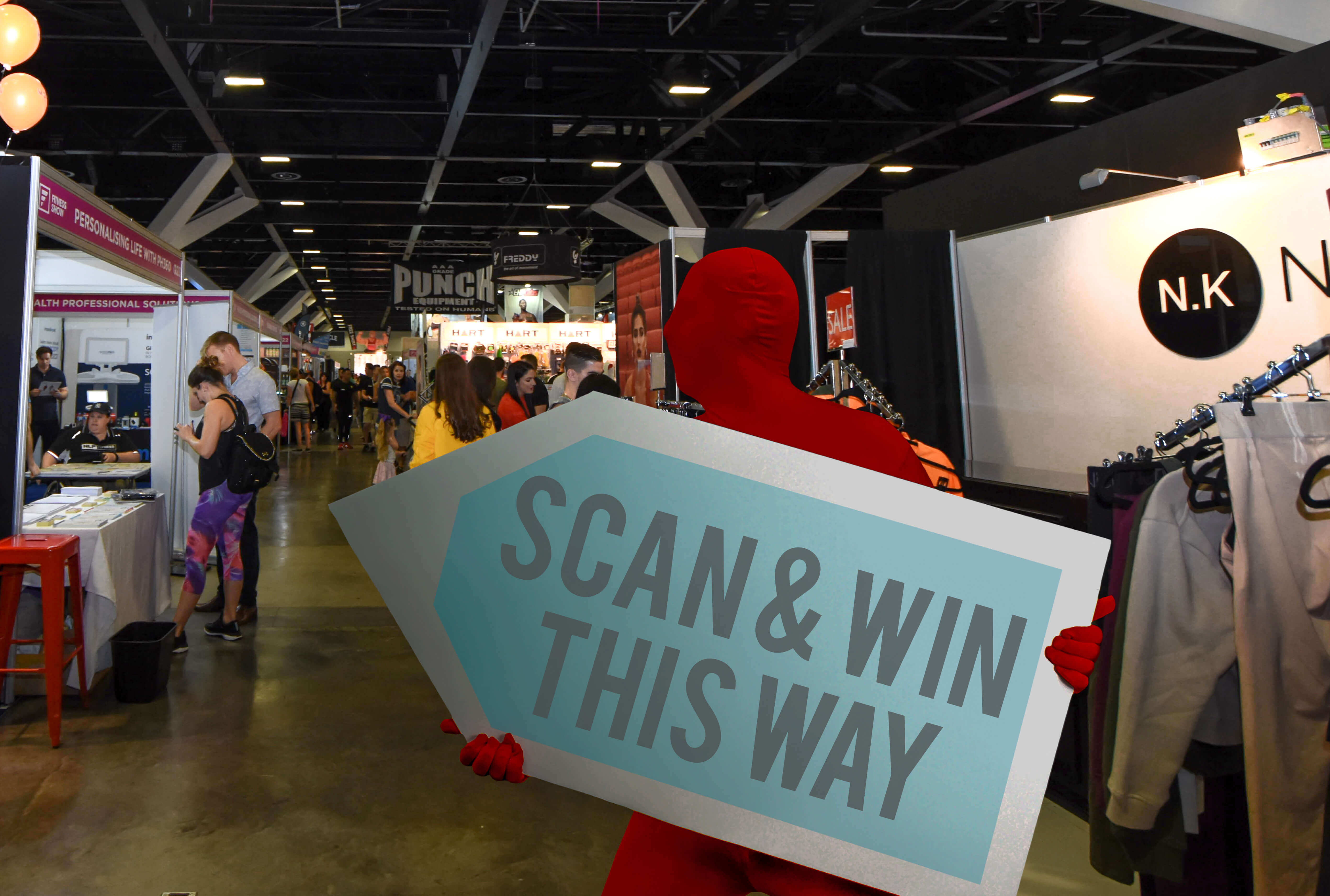 A sign waver holding a promotional sign while wearing a red morph suit during a trade show event
