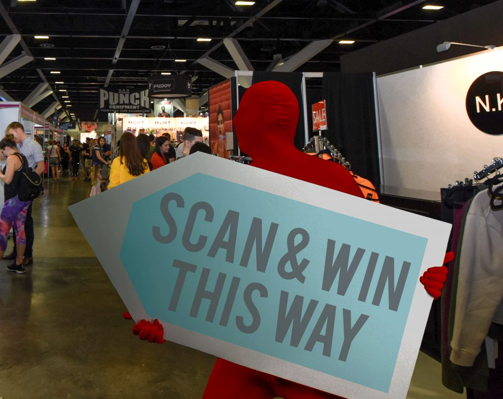 A sign waver holding a large arrow sign while wearing a bright red morph suit during an event