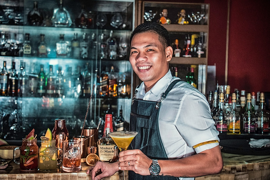 A smiling bartender holding a cocktail