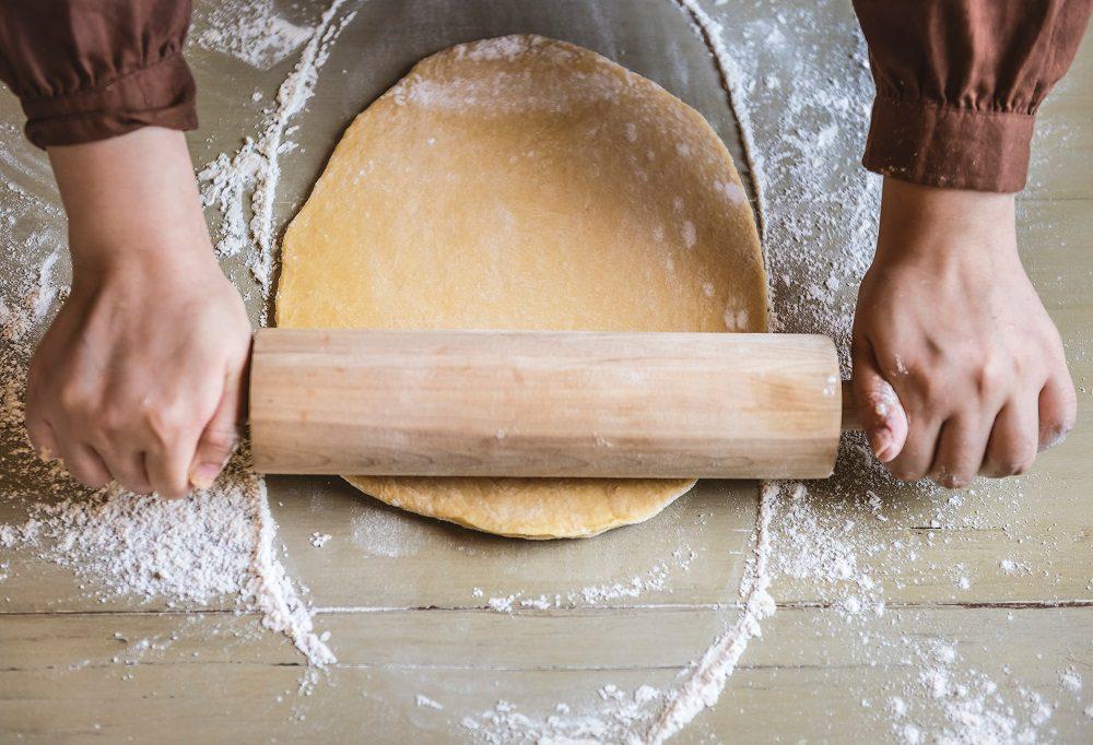 kitchen hand rolling dough